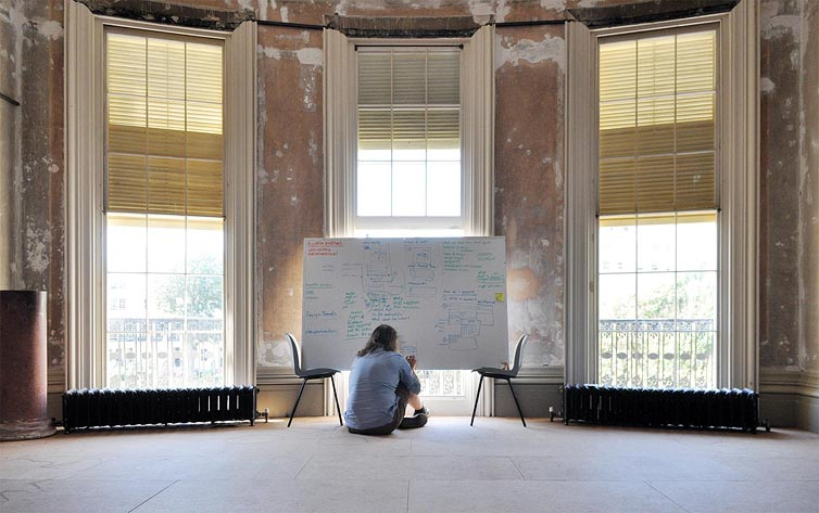 Danny Hope sitting on the floor in front of a whiteboard in an unrestored drawing room.