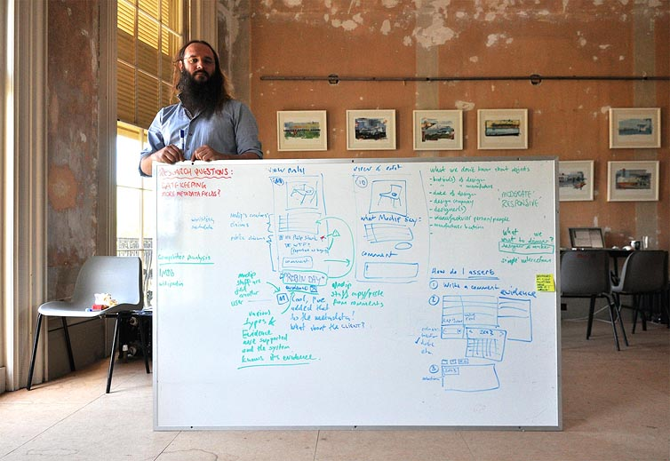 Danny Hoipe standing by a whiteboard in an unrestored drawing room.